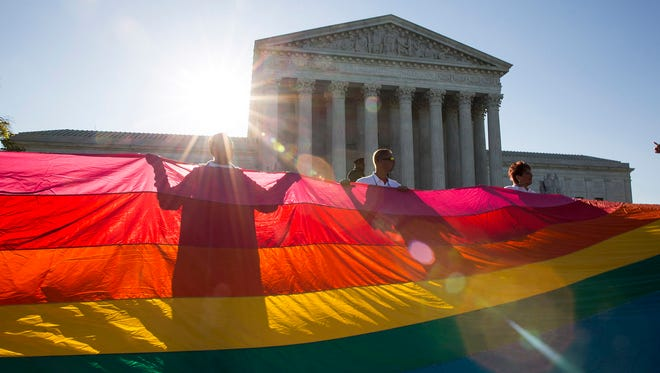 WASHINGTON, DC - APRIL 28: Supporters of same-sex marriage unfurl a large rainbow pride flag near the Supreme Court, April 28, 2015 in Washington, DC. On Tuesday the Supreme Court will hear arguments concerning whether same-sex marriage is a constitutional right, with decisions expected in June. (Drew Angerer/Getty Images) ORG XMIT: 551458191 ORIG FILE ID: 471417686