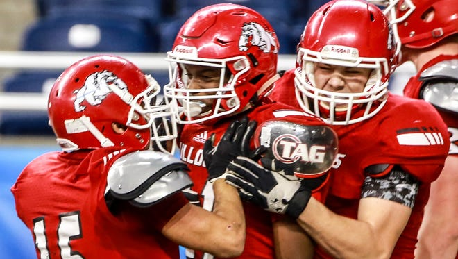 Romeo WR Bradley Tanner, center, celebrates scoring a touchdown with his teammates, Hunberto Flores and Louis Thom, during the first half Michigan High School Athletic Association football Division 1 finals against Detroit Cass Tech at Ford Field in Detroit on Saturday, Nov. 28, 2015.