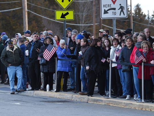People wait for the motorcade to arrive at Stewart