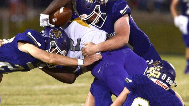 Booneville's Ethan Wooldridge, left, Brett Welling and Rayce Blansett (88) stop Mayflower's Ed Pye for a loss in the first quarter Oct. 9 in Booneville. Booneville won the game 40-7.