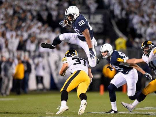 Penn State running back Saquon Barkley leaps over Iowa defensive back Brandon Snyder during the Nittany Lions' 41-14 thumping of the Hawkeyes earlier this month. Barkley leads the Big Ten with 1,205 rushing yards through 11 games.