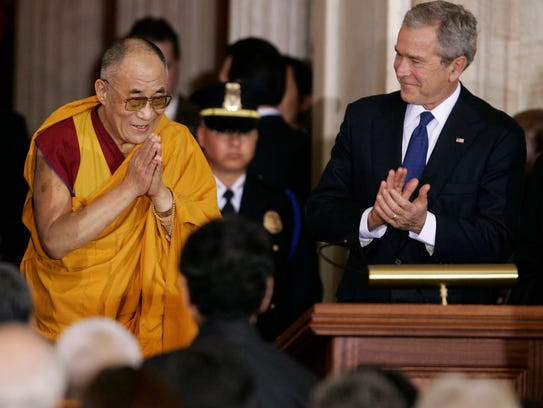 President George W. Bush (right) applauds as the Dalai