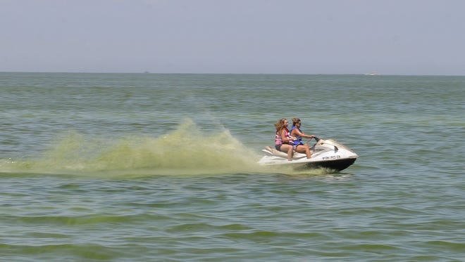 Jet skiers churn up toxic blue-green algae on Lake Erie in Port Clinton in the summer of 2015.
