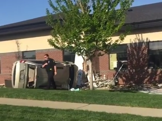 A vehicle rests on its side after hitting a building