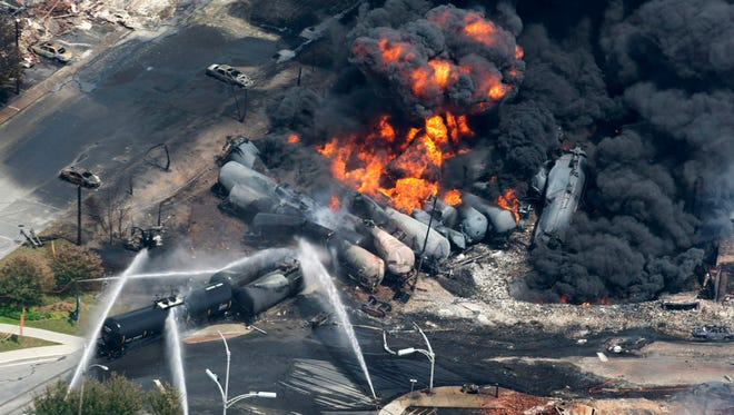 Smoke pours from railway cars carrying crude oil after derailing in downtown Lac-Megantic, Quebec, July 6, 2013.