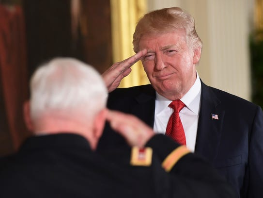 President Donald Trump, right, salutes retired Army