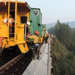 BNSF Brakeman Nick Misecko waits while wildland firefighter Matt Lamb hands a pump to Michael Rudolph as they offload the caboose onto the railroad trestle south of Essex on Tuesday. The wildfire is threatening 200 structures near Glacier National Park.