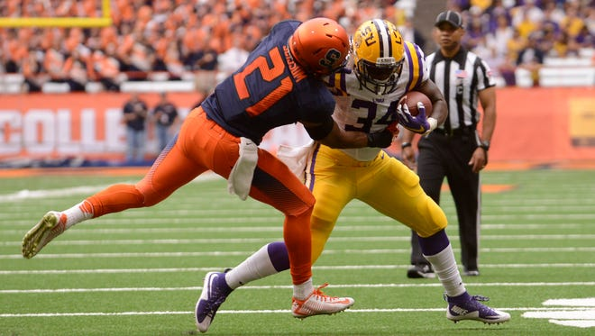 LSU Tigers running back Darrel Williams (34) is tackled by Syracuse Orange safety Chauncey Scissum (21) of Rush-Henrietta. Scissum is recovering from a stabbing attack and is expected to be fine for the 2016 season.