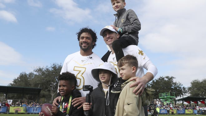 Seattle Seahawks QB Russell Wilson (left) with son Future Zahir Wilburn, and quarterback Drew Brees of the New Orleans Saints with sons Bowen Christopher Brees, Baylen Robert Brees, and Callen Christian Brees pose for a photo after Pro Bowl NFL football practice on Jan. 22, 2020, in Kissimmee, Fla.