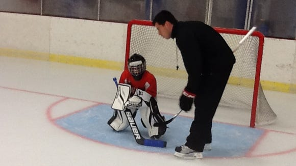 Matt Meacham, the current Chicago Blackhawks video coach, helps a young student at the Southern Tier Goalie School last year.