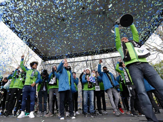 Seattle Sounders midfielder and captain Osvaldo holds up the MLS Cup trophy as confetti flies during a championship rally Tuesday in Seattle.