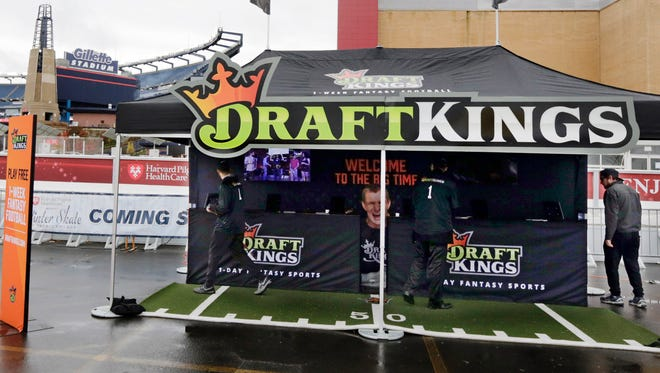 FILE -  In this Oct. 25, 2015, photograph, workers set up a DraftKings promotions tent in the parking lot of Gillette Stadium, in Foxborough, Mass., before an NFL football game between the New England Patriots and New York Jets.