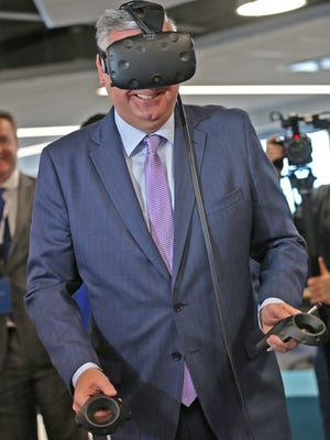 Gov. Eric Holcomb smiles as he tries out a virtual reality device for designing a home, during a tour at the ribbon cutting event for the Infosys tech and innovation hub, Tuesday, Mar. 6, 2018.
