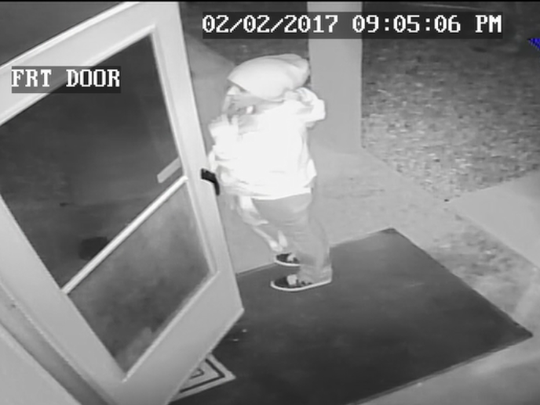 This screenshot from the homeowner's security footage shows the female suspect approach the resident, allegedly asking to use the phone.