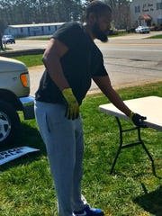 Mike Brice sets up tables for a garage sale on Wrangle Hill Road Saturday.