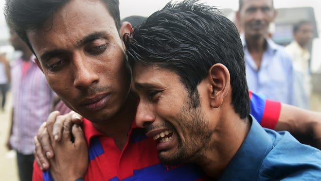 People react after finding the body of a relative following the ferry accident in Bangladesh.