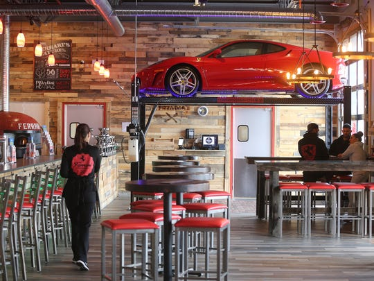 An operational Ferrari on a lift is part of the decor
