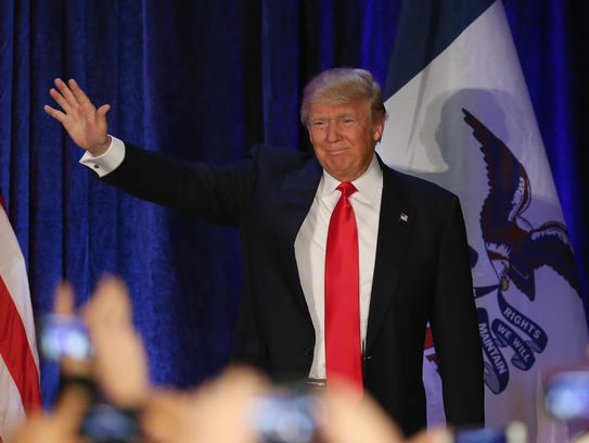 Donald Trump waves at a caucus night gathering in West