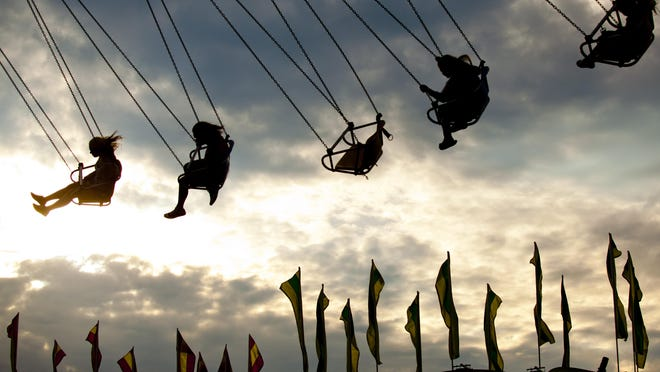 Kids ride on a swinging attraction during Family Night July 16, 2015 in Port Huron.