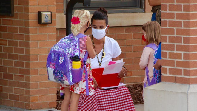 A teacher meets a pair of students on the first day of school in Hamilton Community Schools Wednesday, Aug. 26.