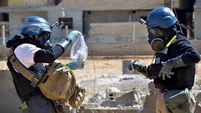Investigators take samples from sand near a part of a missile that was suspected of carrying chemical agents in the countryside of Ain Terma, Syria, in August.