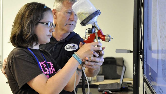 """Seventh-grader Zoe Fiddelke, of Manson, Iowa, gets a hand from instructor Doug Zuspann on June 18 as she learns about auto painting during the annual """"Diva Tech"""" event at Iowa Central Community College in Fort Dodge, Iowa. Organizers say the event exposes young women to careers they may not have considered. Topics covered include electrical systems, computer networking and engineering."""