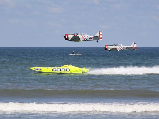 Two World War II-era GEICO Skytyper planes compete against racing catamaran Miss GEICO  at the OC Air Show.