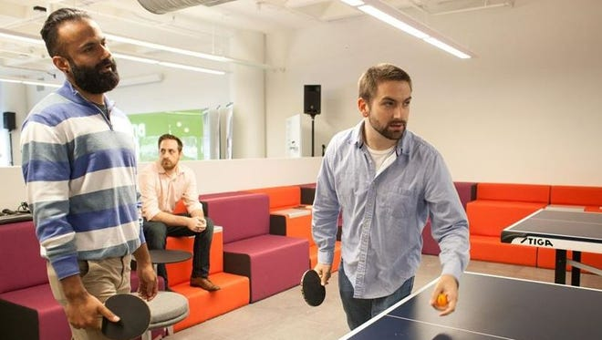Employees play ping-pong at Humana's Digital Experience Center in Louisville.