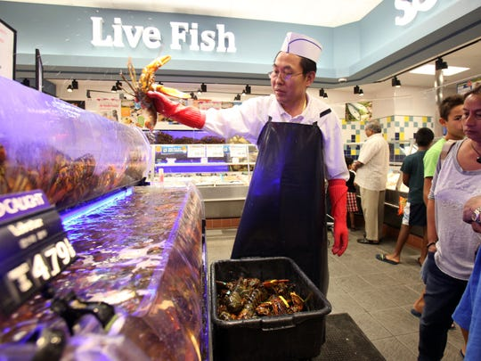 Kui Jin, manager of the fish department, retrieves lobster for customers at H-Mart supermarket in Hartsdale.