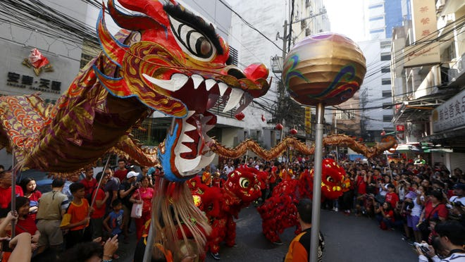 In this Feb. 5, 2019, photo, dancers perform traditional lion and dragon dances in celebration of the Lunar New Year in the Chinatown district in Manila, Philippines. This year is the Year of the Earth Pig on the Chinese Lunar calendar and is supposed to represent abundance, diligence and generosity.