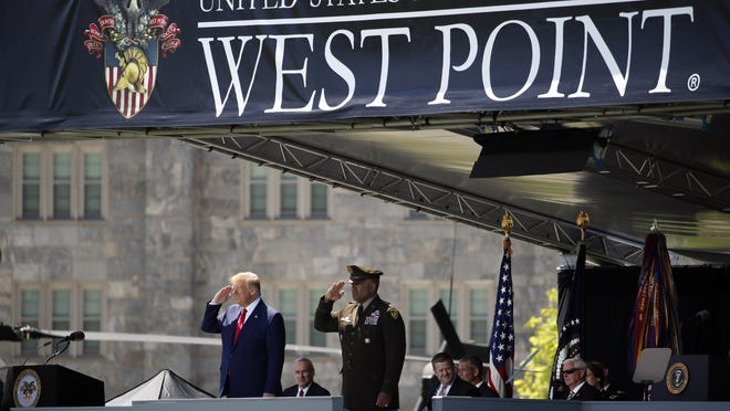 President Donald Trump, left, and United States Military Academy Lt. Gen. Darryl Williams, right, salute Saturday during a commencement ceremony on the parade field, at the United States Military Academy in West Point.