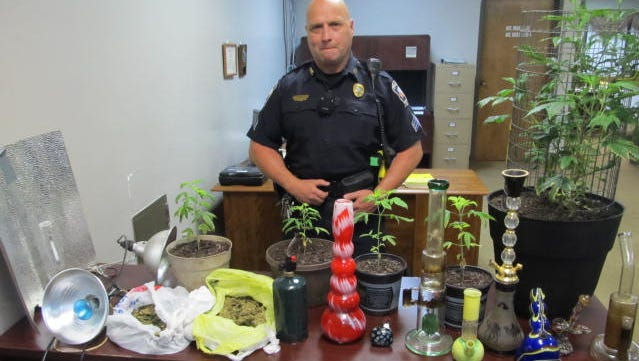 Investigator Joey Hedge with items seized during a drug raid at a Browning Avenue home.