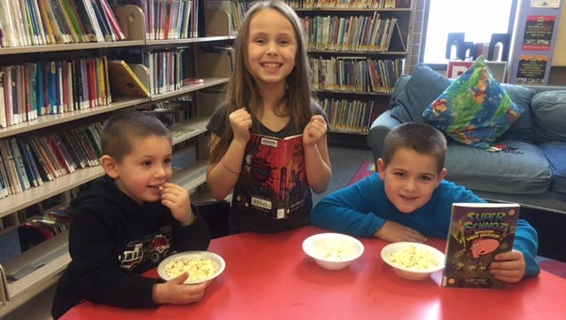 (From left) Cayden Brooks, 4, Abigail Sparks, 8, and Mark Anthony Messeck, 8, enjoyed books and popcorn a the Cumberland County Library as part of National Popcorn Day!