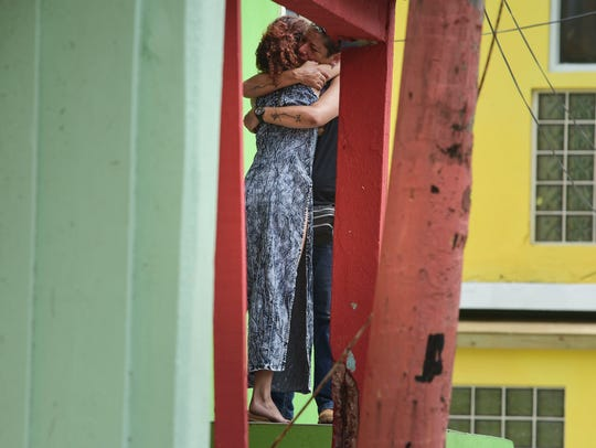 Residents in Old San Juan comfort one another as the