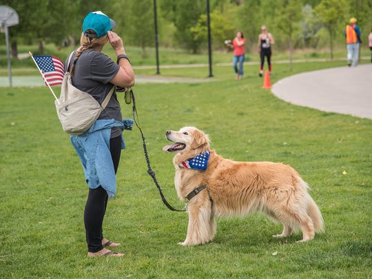 Sarah Bucko waits with her dog Caymus near the finish   line of the Colorado Run, a 10K race beginning in Cottonwood Glen Park on Monday, May 28, 2018.