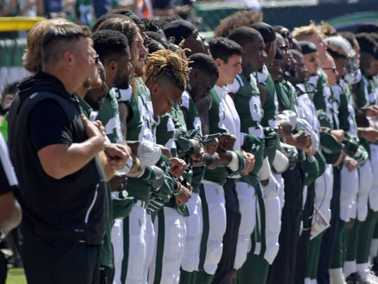 New York Jets players lock arms during the playing of the national anthem against the Miami Dolphins before an NFL football game Sunday, Sept. 24, 2017, in East Rutherford, N.J. (AP Photo/Bill Kostroun)