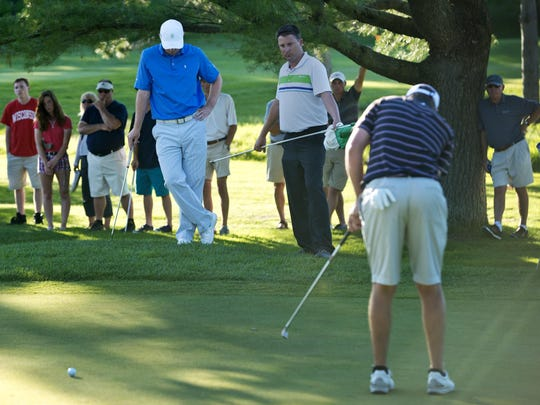Evan Russell (left, in white cap) can't watch as Bryan Smith hits and misses a putt during their five-hole playoff in the 2014 Vermont Amateur golf tournament at the Burlington Country Club.