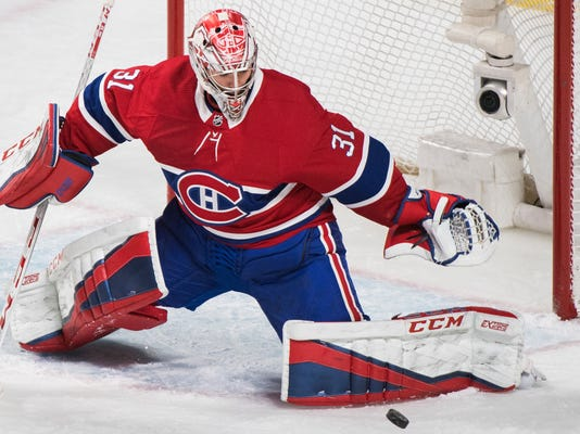 Montreal Canadiens goaltender Carey Price makes a save against the New Jersey Devils during the first period of an NHL hockey game in Montreal, Sunday, April 1, 2018. (Graham Hughes/The Canadian Press via AP)