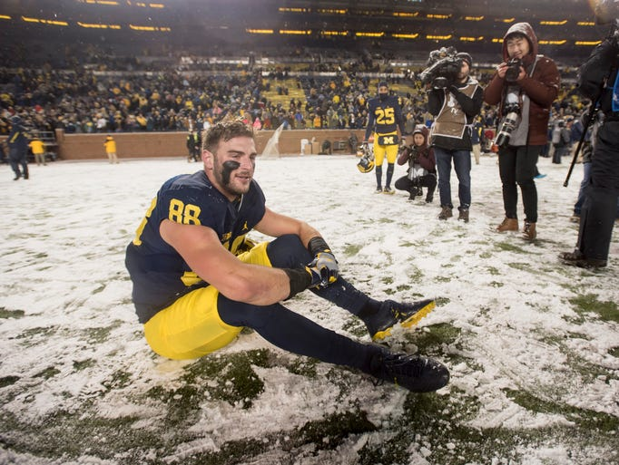 Michigan tight end Jake Butt sits in the snow and takes