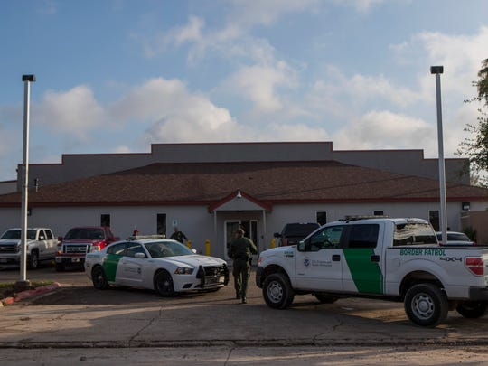 Border Patrol agents stand guard outside the Border