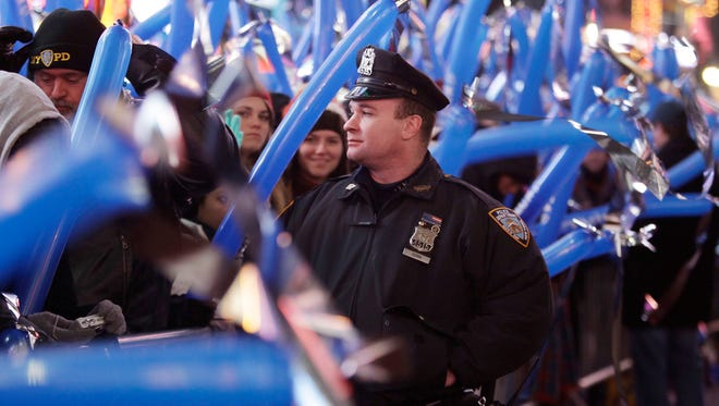 A New York City police officer watches the crowd on New Year's Eve 2009 in Times Square.  New York remained the USA's third most populous state in 2013, the Census Bureau reports.
