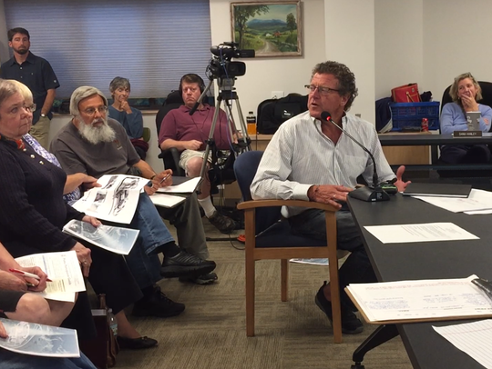 Developer Peter Edelmann, seated at table, discusses
