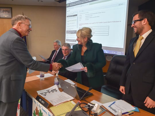 Joan Smith, pictured shaking hands with fellow CASD board member Carl Barton at the board's reorganization meeting in December, was the lone incumbent to be re-elected to the embattled school board. She and four new members are helping usher in a new era for the board.