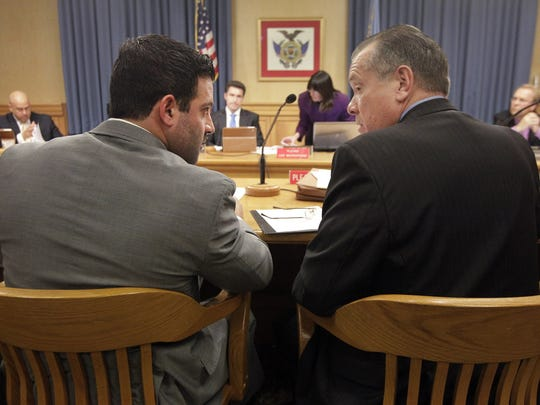 Jon Ferraro confers with his attorney at a city hearing