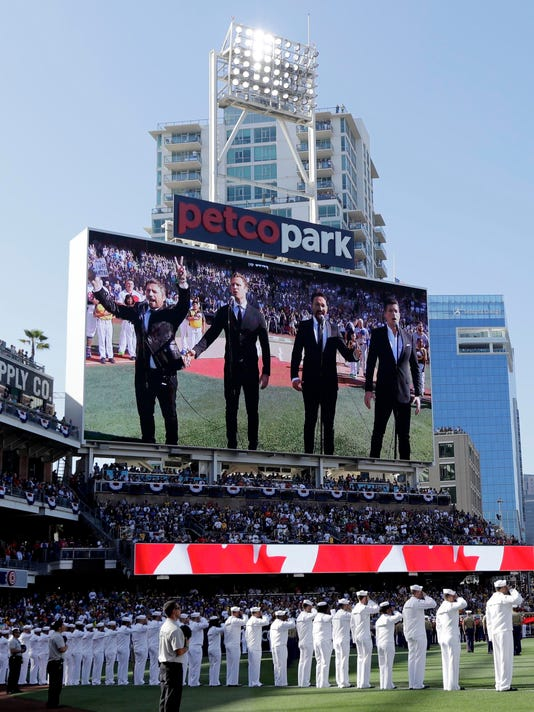 "FILE - In this Tuesday, July 12, 2016 file photo, The Tenors, shown on the scoreboard, perform during the Canadian National Anthem prior to the MLB baseball All-Star Game, in San Diego. A member of a Canadian singing quartet changed a lyric in his country's national anthem and held up a sign proclaiming ""All Lives Matter"" during a pregame performance at the 87th All-Star Game on Tuesday. The Tenors, a group based in British Columbia, caused a stir at Petco Park with Remigio Pereira's actions while singing ""O Canada."" (AP Photo/Gregory Bull, File)"