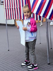 Trinidy Young, 4,  carries a ballot  for her mother,