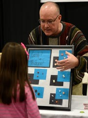 Tom Bergmann of Aurora BayCare Medical Center shows kids how candy can look like medicine during Saturday's Superbowl of Safety event at the KI Convention Center in downtown Green Bay.
