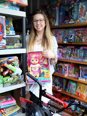 Jenny Williams, founder of Candle Wishes birthday foundation, stands next to some of the items that the group has collected to give to kids for their birthdays.