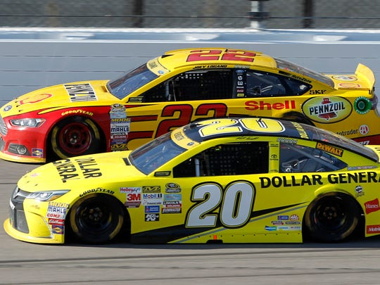 Sprint Cup Series driver Joey Logano (22) and Matt Kenseth (20) run side-by-side during a NASCAR auto race at Kansas Speedway in Kansas City, Kan., Oct. 18, 2015.