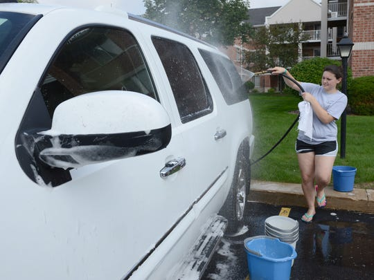 "St. Norbert College student Morgan Eilers, of Waupaca, helps wash cars at the Nicolet Highlands Senior Apatments, as part of the eleventh annual ""Into the Streets"" community service event."